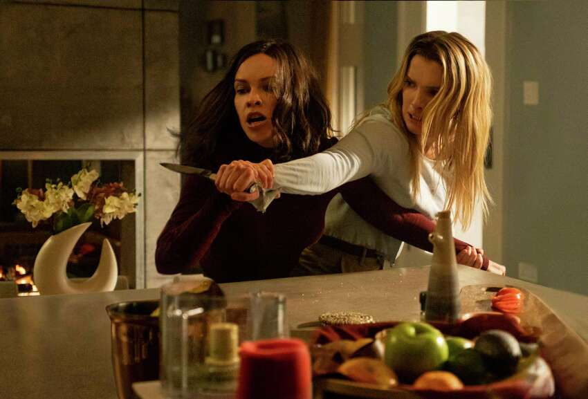 This image released by Universal Pictures shows Hilary Swank, left, and Betty Gilpin in a scene from