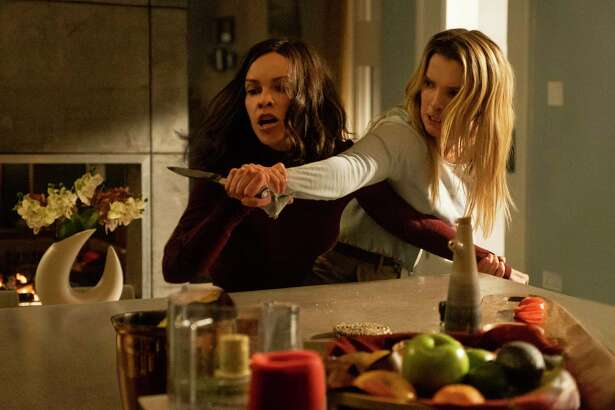 "This image released by Universal Pictures shows Hilary Swank, left, and Betty Gilpin in a scene from ""The Hunt."" (Patti Perret/Universal Pictures via AP)"