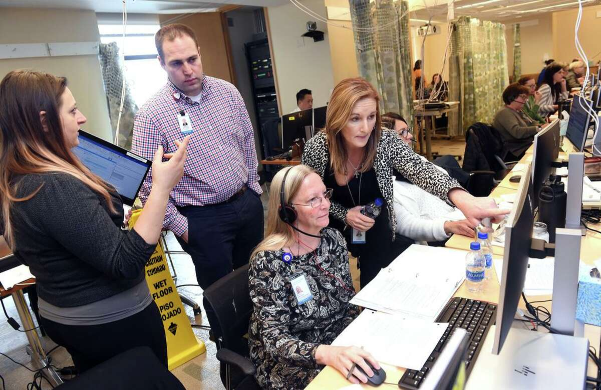 From left, Samantha Fonda, Joshua Williston, Betsy Hine and Stacey Lane collaborate with calls at the Covid-19 Call Center at Yale New Haven Health in Yale New Haven Hospital.