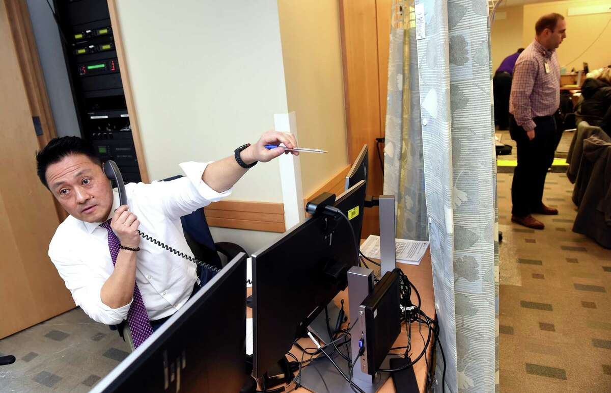 Dr. Steven Choi (left), chief quality officer at Yale New Haven Health System and the Yale School of Medicine, works at the Covid-19 Call Center at Yale New Haven Health in Yale New Haven Hospital on March 12, 2020.