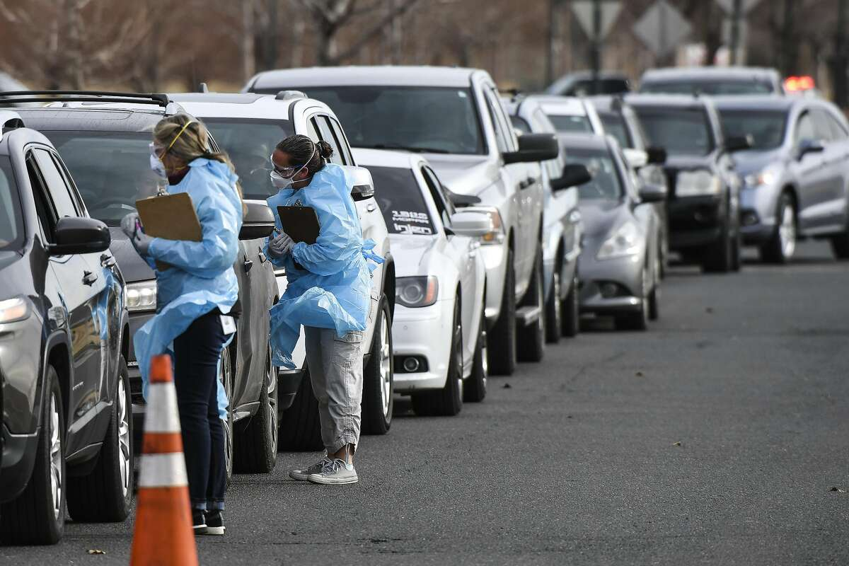 DENVER, CO - MARCH 12: Healthcare workers from the Colorado Department of Public Health and Environment check in with people waiting to be tested for COVID-19 at the state's first drive-up testing center on March 12, 2020 in Denver, Colorado. The testing center is free and available to anyone who has a note from a doctor confirming they meet the criteria to be tested for the virus. (Photo by Michael Ciaglo/Getty Images)