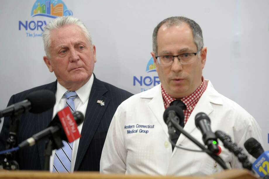 Dr. Paolo Pino, Norwalk Hospital's Chief of Infectious Diseases, speaks during a news conference at City Hall in Norwalk, Conn. March 5, 2020, while Norwalk Mayor Harry Rilling, left, looks on. Rilling declared a local state of civil preparedness emergency on March 14, 2020. Photo: Ned Gerard / Hearst Connecticut Media / Connecticut Post