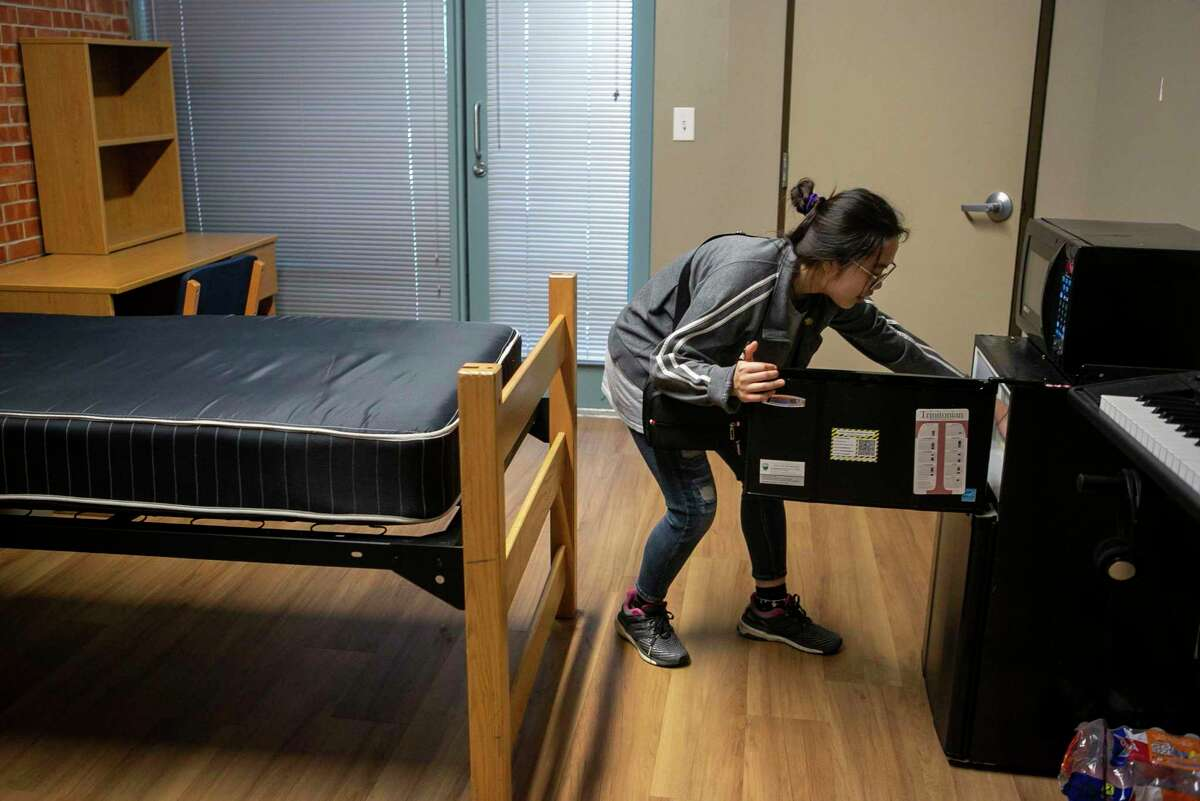 Mai-Vo, 19, makes sure her mini-fridge is empty after packing up her Trinity University dorm room. Trinity decided to close it residence halls for the last five weeks of the semester as a precaution against the coronavirus.