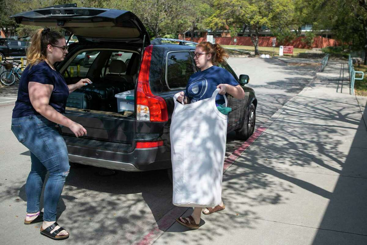 Hunter Atherton, left, and Shelby Atherton, right, both of San Antonio, move Shelby out of her Trinity University dorm. Students will finish the semester with online instruction.