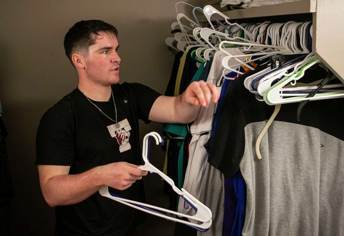 Colin Conway, 21, of Houston gathers up hangers and clothes as he moves out of his Trinity University dorm.