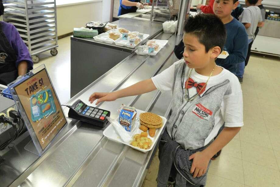 Chrisyian Rueda grabs his lunch in the cafeteria at Tracey School in Norwalk in 2017. Photo: Alex Von Kleydorff / Hearst Connecticut Media / Norwalk Hour