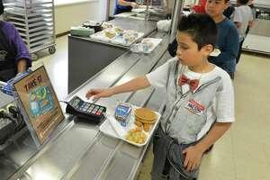 Chrisyian Rueda grabs his lunch in the cafeteria at Tracey School in Norwalk in 2017.