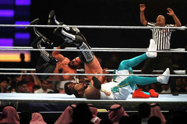 Seth Rollins and Murphy, left and center, in action against The Street Prophets at WWE Super ShowDown in Riyadh, Saudi Arabia, late Thursday, Feb. 27, 2020. (AP Photo/Amr Nabil)