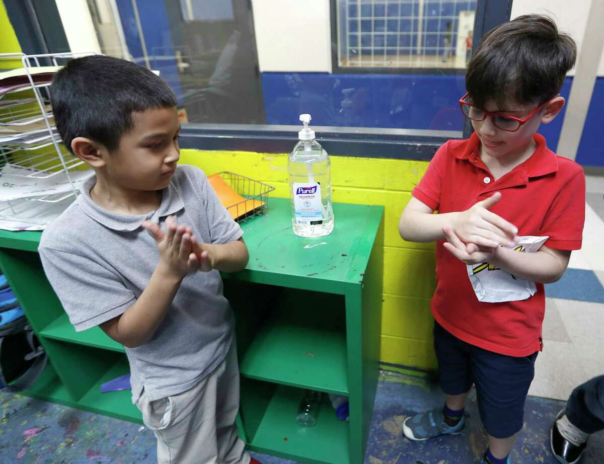 Victor Parache, 6, left, and Emiliano Arango, 7, use the hand sanitizer at the Heights Boys and Girls Club, in Houston,Thursday, March 12, 2020. While local health officials are still recommending that schools remain open amid coronavirus fears, the looming threat of canceling K-12 classes means parents are making child care plans and local organizations are making preliminary plans to accommodate kids. Experts said the region's experience with recent natural disasters and the gradual ramp-up of the coronavirus gives time for agencies to make preparations. Still, parents are concerned about student health and school cancellations could be difficult for working parents without easy access to child care.