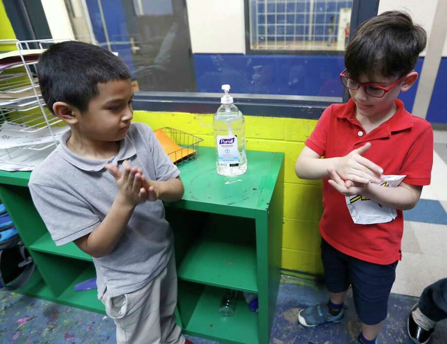 Victor Parache, 6, left, and Emiliano Arango, 7, use the hand sanitizer at the Heights Boys and Girls Club, in Houston,Thursday, March 12, 2020. While local health officials are still recommending that schools remain open amid coronavirus fears, the looming threat of canceling K-12 classes means parents are making child care plans and local organizations are making preliminary plans to accommodate kids. Experts said the region's experience with recent natural disasters and the gradual ramp-up of the coronavirus gives time for agencies to make preparations. Still, parents are concerned about student health and school cancellations could be difficult for working parents without easy access to child care. Photo: Karen Warren, Staff Photographer / © 2020 Houston Chronicle