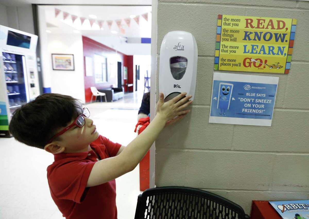 Emiliano Arango, 7, uses the hand sanitizer at the Heights Boys and Girls Club, in Houston,Thursday, March 12, 2020. While local health officials are still recommending that schools remain open amid coronavirus fears, the looming threat of canceling K-12 classes means parents are making child care plans and local organizations are making preliminary plans to accommodate kids. Experts said the region's experience with recent natural disasters and the gradual ramp-up of the coronavirus gives time for agencies to make preparations. Still, parents are concerned about student health and school cancellations could be difficult for working parents without easy access to child care.