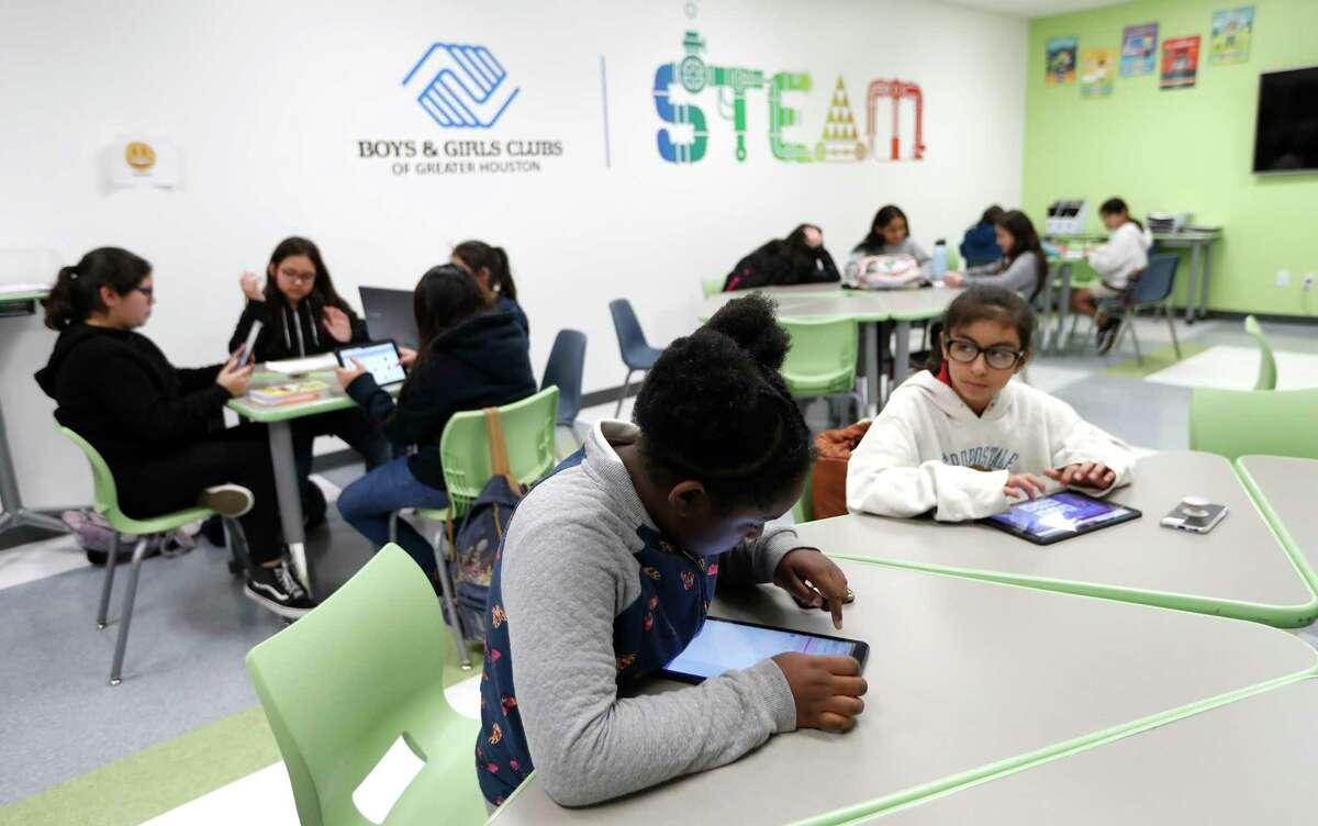 Girls do homework during Power Hour in a classroom at the Heights Boys and Girls Club, in Houston,Thursday, March 12, 2020. While local health officials are still recommending that schools remain open amid coronavirus fears, the looming threat of canceling K-12 classes means parents are making child care plans and local organizations are making preliminary plans to accommodate kids. Experts said the region's experience with recent natural disasters and the gradual ramp-up of the coronavirus gives time for agencies to make preparations. Still, parents are concerned about student health and school cancellations could be difficult for working parents without easy access to child care.