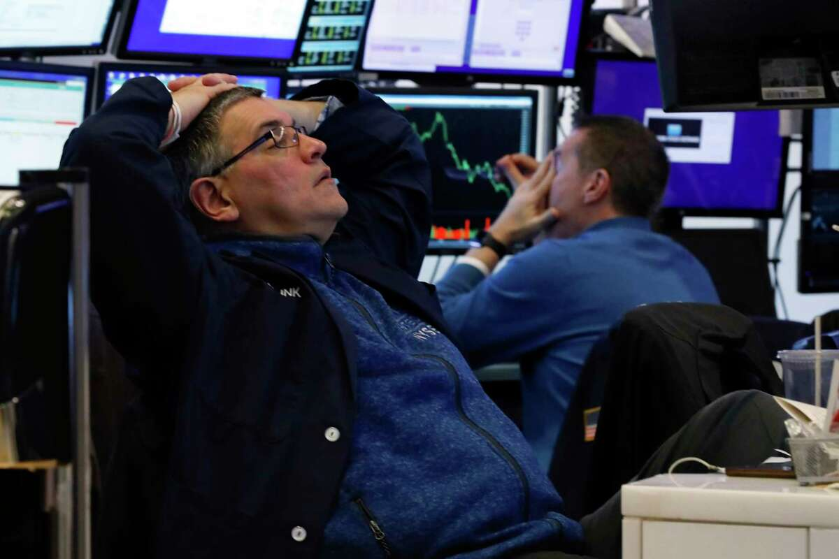 A pair of traders work in their booth on the floor of the New York Stock Exchange, Thursday, March 12, 2020. The deepening coronavirus crisis is sending stocks into another alarming slide on Wall Street, triggering a brief, automatic shutdown in trading for the second time this week. (AP Photo/Richard Drew)