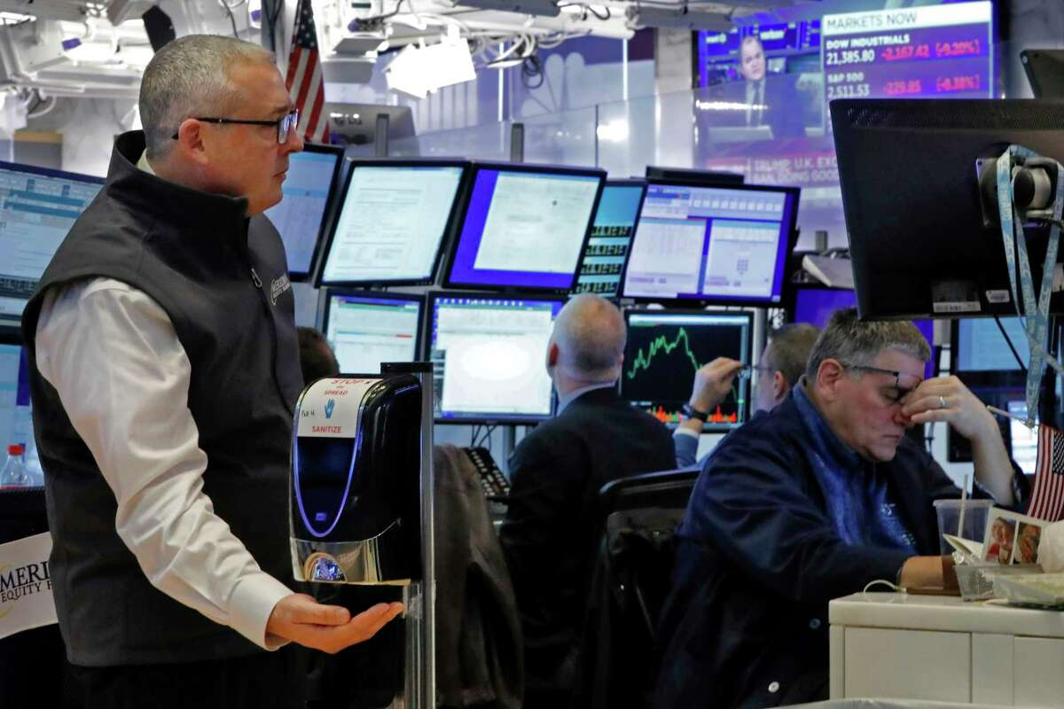 A trader uses a hand sanitizer dispenser on the floor of the New York Stock Exchange, Thursday, March 12, 2020. The deepening coronavirus crisis is sending stocks into another alarming slide on Wall Street, triggering a brief, automatic shutdown in trading for the second time this week. (AP Photo/Richard Drew)