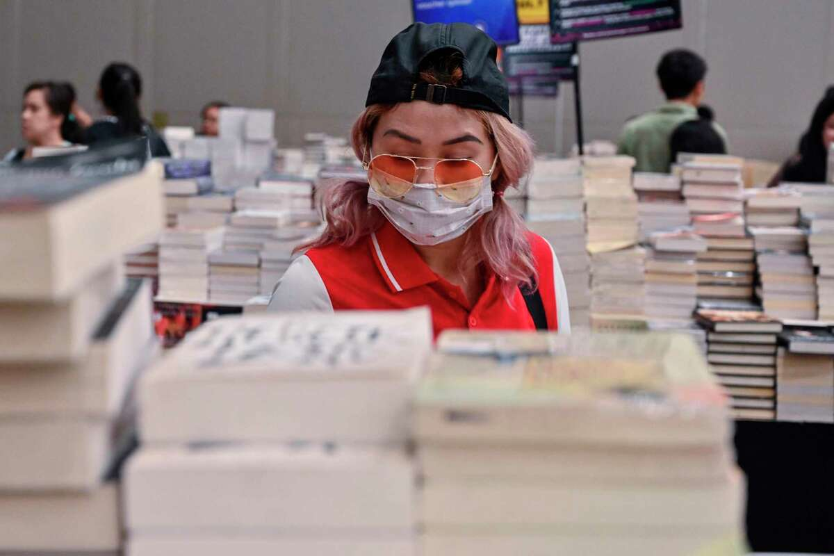 A visitor, wearing a facemask as a preventive measure against the COVID-19 coronavirus, browses for books during the 'Big Bad Wolf Books' book fair in Jakarta on March 8, 2020. (Photo by ADEK BERRY / AFP) (Photo by ADEK BERRY/AFP via Getty Images)