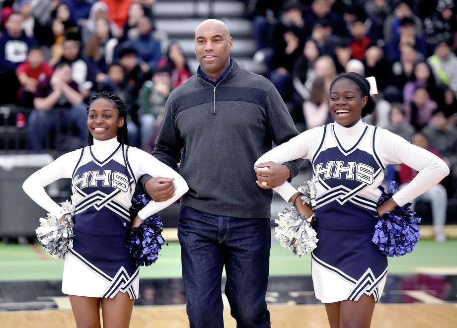 Southern Connecticut State University men's basketball head coach and former professional basketball and baseball player Scott Burrell (center) is escorted to center stage by Hillhouse High School cheerleaders Angelie Alcin (left) and Kuniya Asobayire (right) during the Walter Camp Staying in School Rally at the Floyd Little Athletic Center in New Haven on January 10, 2019. Photo: Arnold Gold / Hearst Connecticut Media / New Haven Register