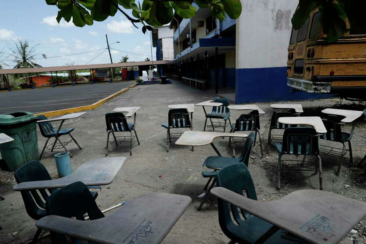 Student desks sit in the shade next to the parking lot of the closed Francisco Beckman high school, where a professor who died of the coronavirus worked, on the outskirts of Panama City, Thursday, March 12, 2020, on the first day that schools closed nation-wide. The vast majority of people recover from the new virus. (AP Photo/Arnulfo Franco)