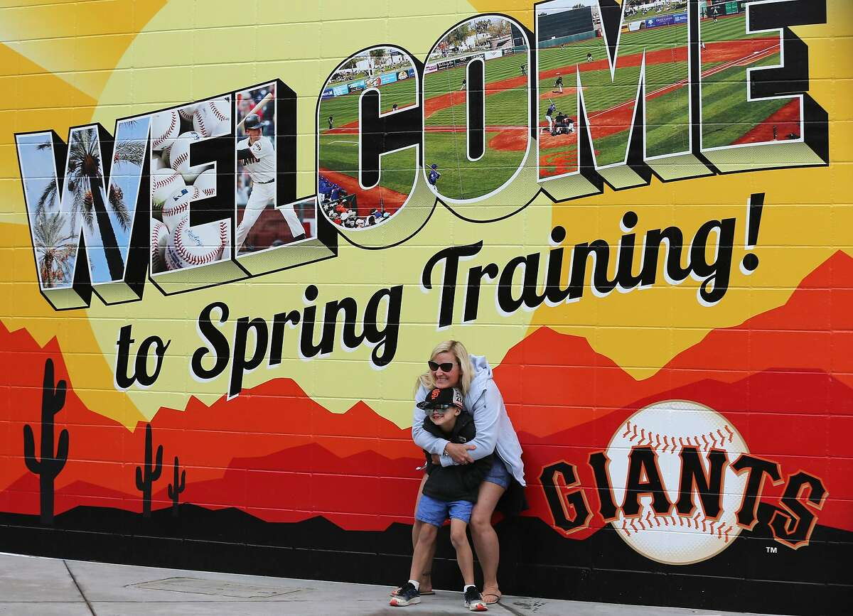 Inside of Scottsdale Stadium San Francisco Giants fans Jessica Lockwood and her son Charly 7, of Menlo Park, try to embrace their unfortunate situation after it was announced that Spring Training games have been suspended Thursday, March 12, 2020, Scottsdale, Arizona.