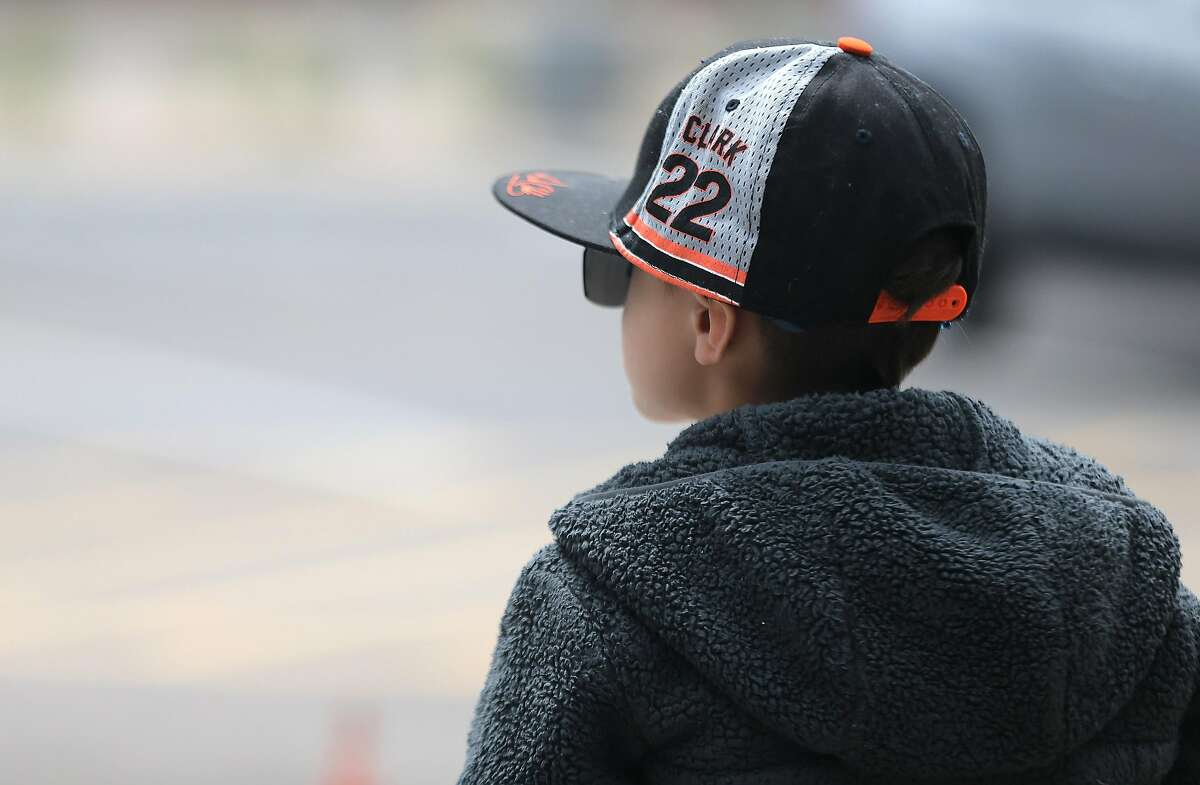 Dejected San Francisco Giants' fan Charly Lockwood 7, of Menlo Park, California sits outside of Scottsdale Stadium after it was announced that Spring Training play has been suspended Thursday, March 12, 2020, Scottsdale, Arizona.