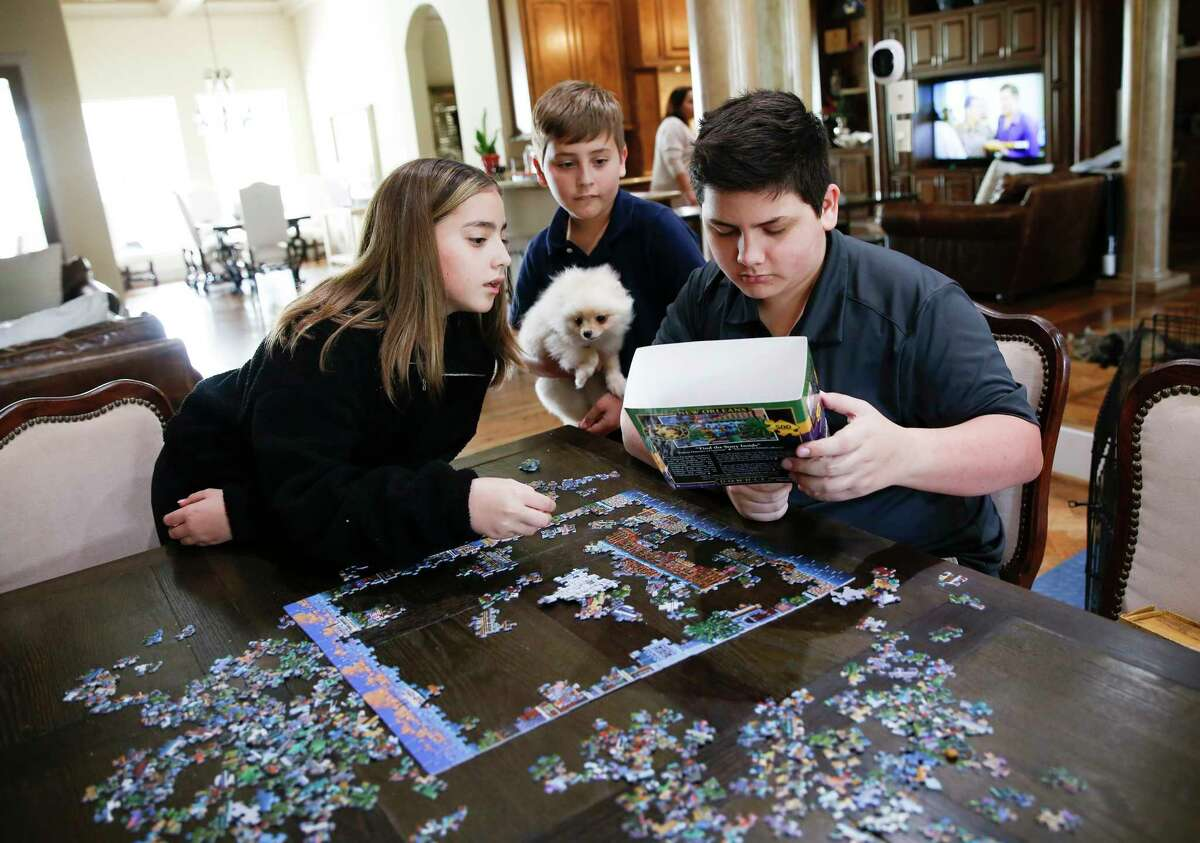 Megan, 12, puppy Coco, Jimmy, 9, and Alex, 15, Goode work on a puzzle in their home as they are self quarantined in their Houston home on Thursday, March 12, 2020.