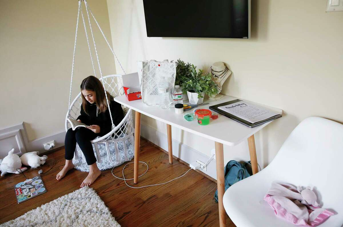 Megan Goode, 12, reads a book in her room as her family is self quarantined in their Houston home on Thursday, March 12, 2020.