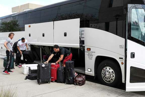 Gear is unloaded from the bus of the UH men's basketball team after it arrived back on campus Thursday.