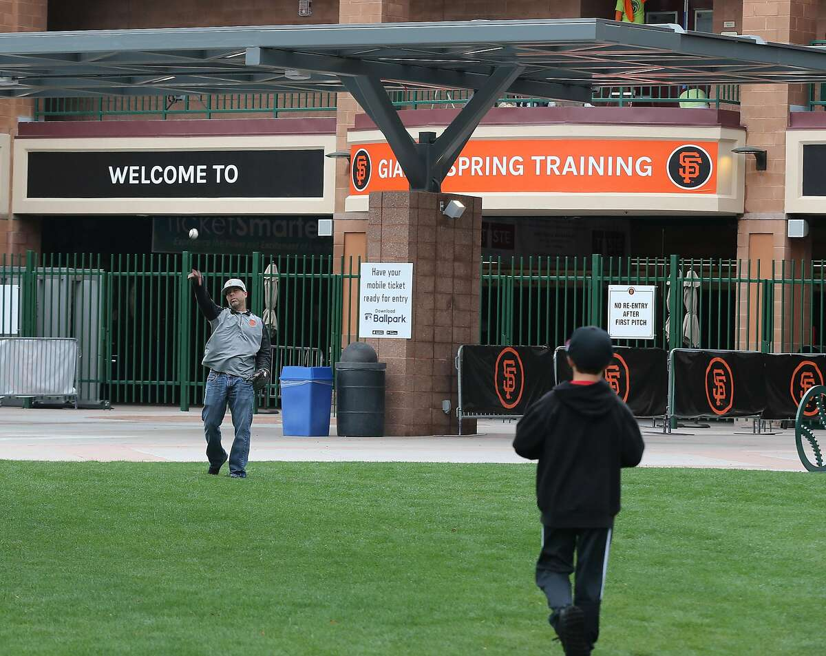 Outside of Scottsdale Stadium San Francisco Giants fans Ryan and Luke Winton 10, of Oakdale play catch after it was announced that Spring Training games have been suspended Thursday, March 12, 2020, Scottsdale, Arizona.