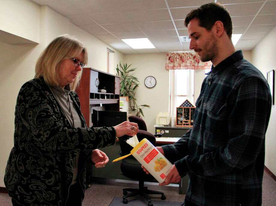 Big Rapids Income Tax Administrator Thomas Paul hands Big Rapids Neighborhood Services Coordinator Cindy Plautz disinfectant wipes as they clean the office for the evening. (Pioneer photo/Alicia Jaimes)