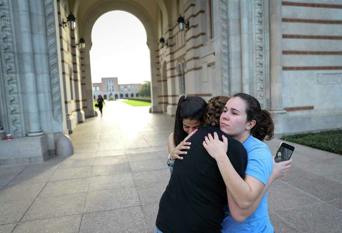 """Alessi Armengol, from right, a senior, hugs her friend Katie Fagundes and her roommate of three years Julia Greenberg outside of Lovett Hall on Thursday, March 12, 2020, at Rice University of Houston in Houston. Campus officials announced that classes would move online for the remainder of the semester due to concerns about COVID-19. The group came to take a photo of Armengol walking through the sally port, which she said one doesn't do until graduation, because they might not be able to do it later. """"It's really sad, Rice has become my home,"""" Greenberg said. """"The people here have been the strongest network for me."""""""