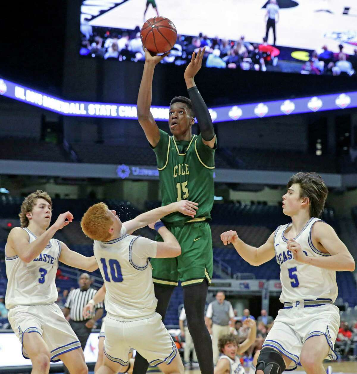 Vince Iwuchukwu gets off a jumper in a crowd during the class 3A state semifinal boys basketball game between Cole and Peaster at the Alamodome on Feb. 12, 2020.