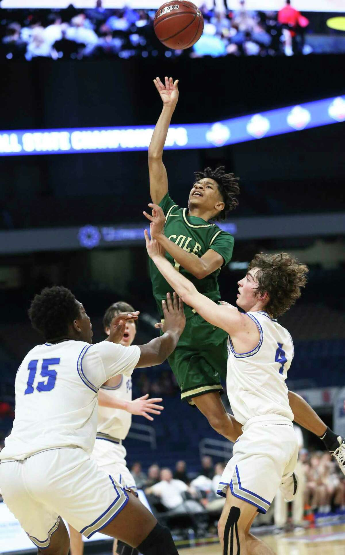 Cougar guard Silas Livingston gets off a jumper during the class 3A state semifinal boys basketball game between Cole and Peaster at the Alamodome on Feb. 12, 2020.