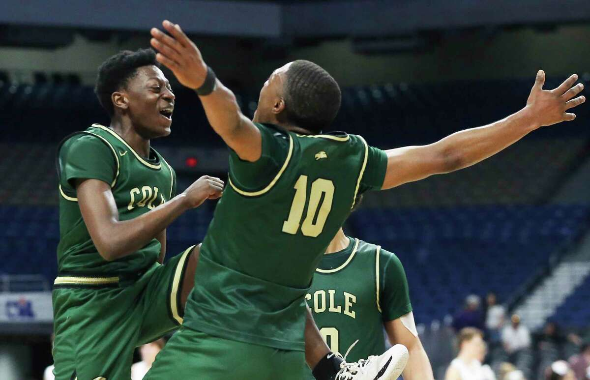 Adreaell Ray, left, and Andrew Reed celebrate the victory after the class 3A state semifinal boys basketball game between Cole and Peaster at the Alamodome on Feb. 12, 2020.