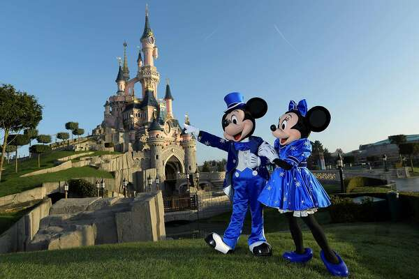 (FILES) In this file photo Disney characters Mickey and Mini mouse pose on March 16, 2017 in front of the Sleeping Beauty Castle to mark the 25th anniversary of Disneyland - originally Euro Disney Resort - in Marne-La-Vallee, east of the French capital Paris. - Disney to shut Florida and Paris theme parks, cruise line over virus: statement (Photo by BERTRAND GUAY / AFP) (Photo by BERTRAND GUAY/AFP via Getty Images)