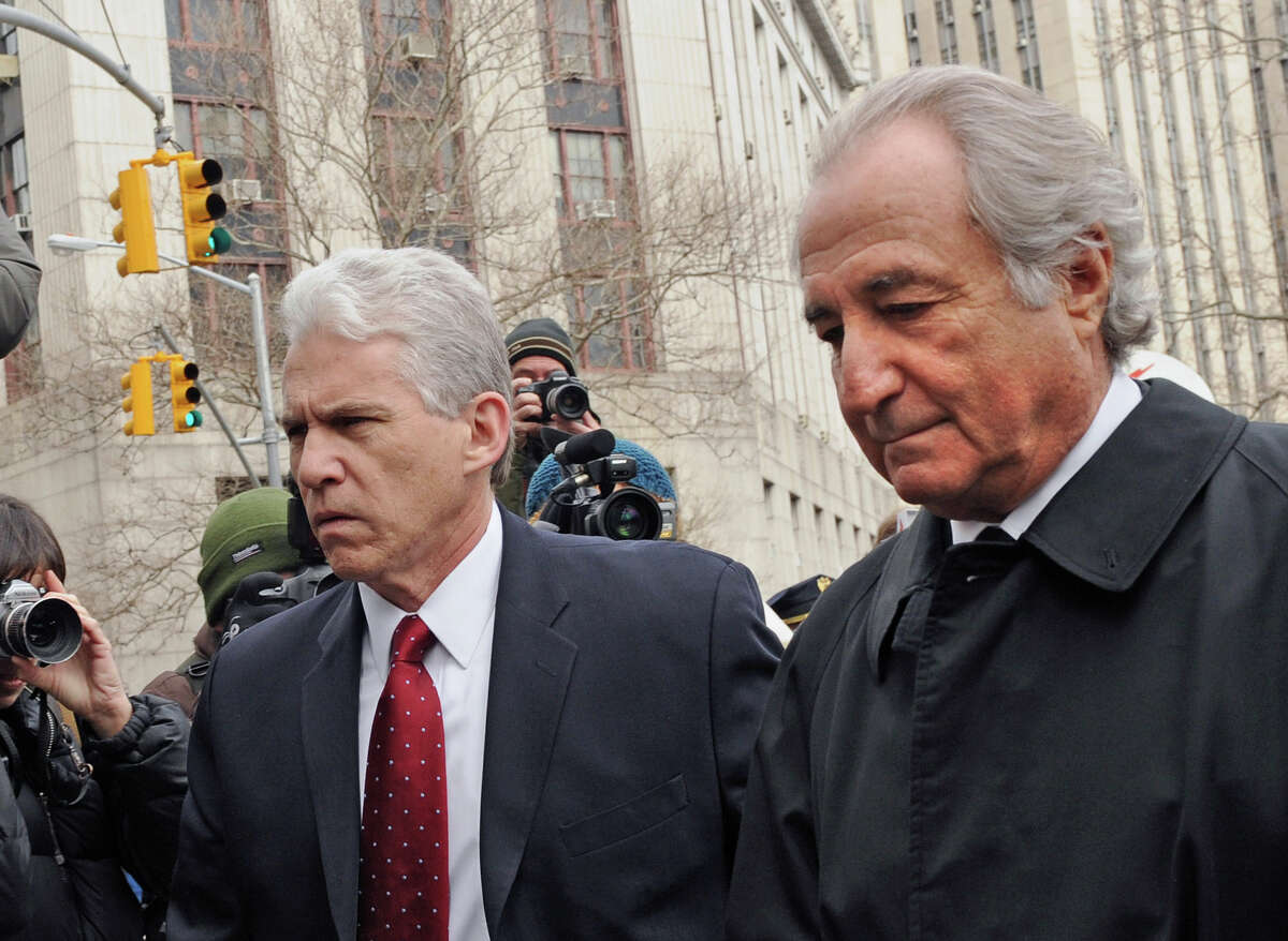 FILE - In this March 10, 2009 file photo, Bernard Madoff, right, arrives at Manhattan federal court in New York. Citing the scope and magnitude of his decades-long Ponzi scheme that cost thousands of investors billions of dollars, federal prosecutors do not support a compassionate release from prison for 81-year-old Madoff, who may only have 18 months to live. (AP Photo/ Louis Lanzano, File)