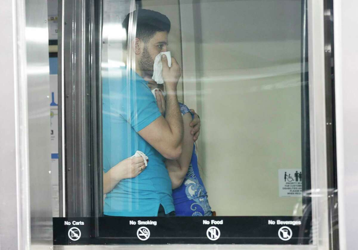 A man and woman covers their mouths while riding the shuttle out of Terminal E at George Bush Intercontinental Airport on Thursday, March 12, 2020, in Houston. The new coronavirus has been classified as a pandemic.