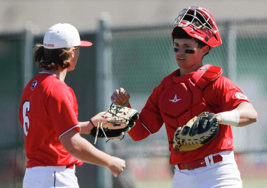 The Woodlands catcher Drew Romo (8) gives relief pitcher Cody Howard a high-five during a non-district high school baseball game at Kingwood Park High School, Thursday, Feb. 27, 2020, in Kingwood. The Woodlands defeated Kingwood Park 10-0. Photo: Jason Fochtman, Houston Chronicle / Staff Photographer / Houston Chronicle © 2020