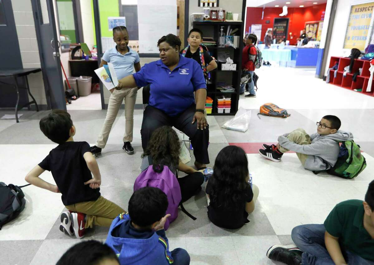 Myra Coleman, lead staffer reads to children at the Heights Boys and Girls Club, in Houston, Thursday, March 12, 2020. While local health officials are still recommending that schools remain open amid coronavirus fears, most area school districts announced they would close for at least a week.