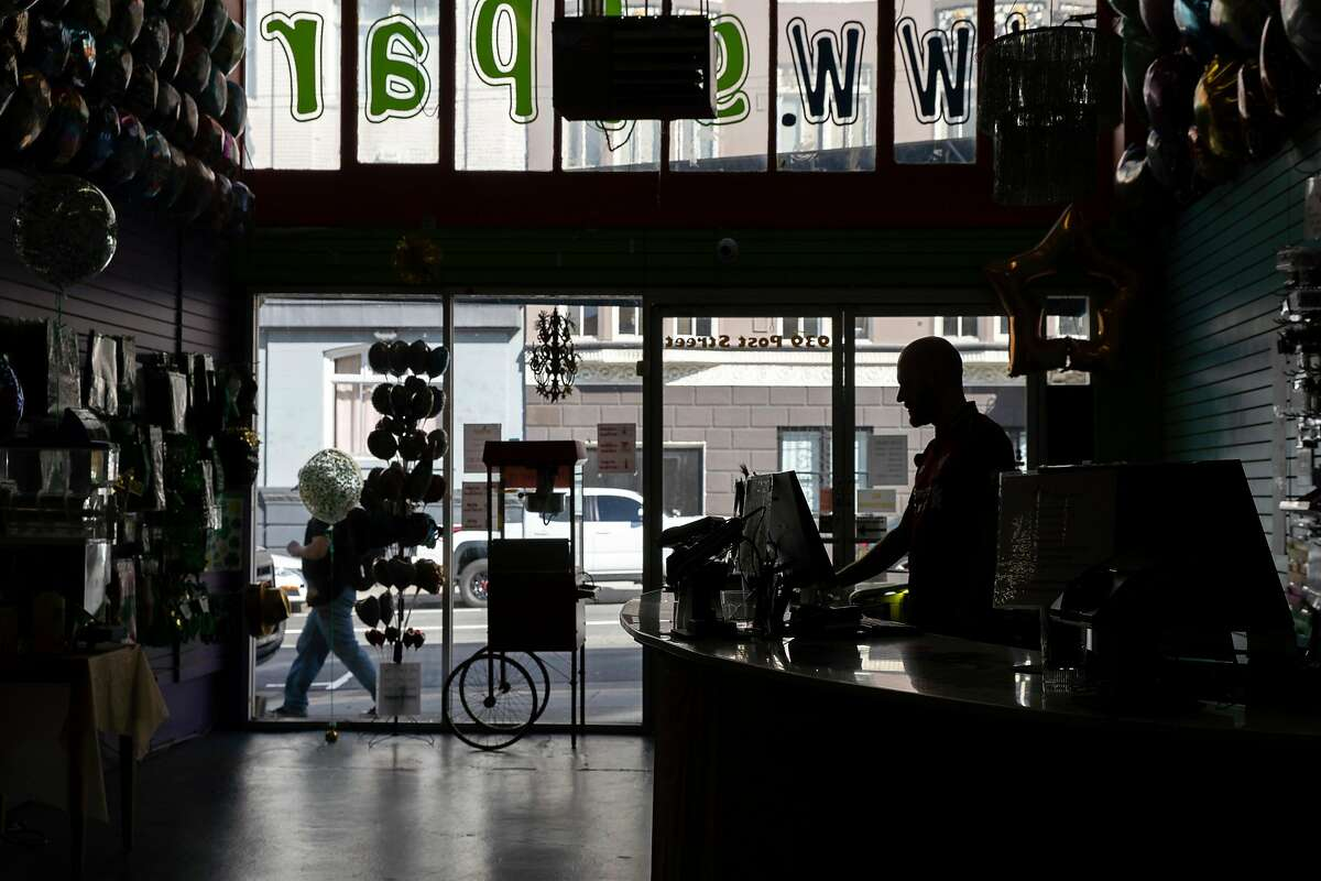 Michael Hinks waits for customers at SF Party, Thursday, March 12, 2020, in San Francisco, Calif. The party store, located at 939 Post St, said it has seen a decline in business because of the coronavirus pandemic.