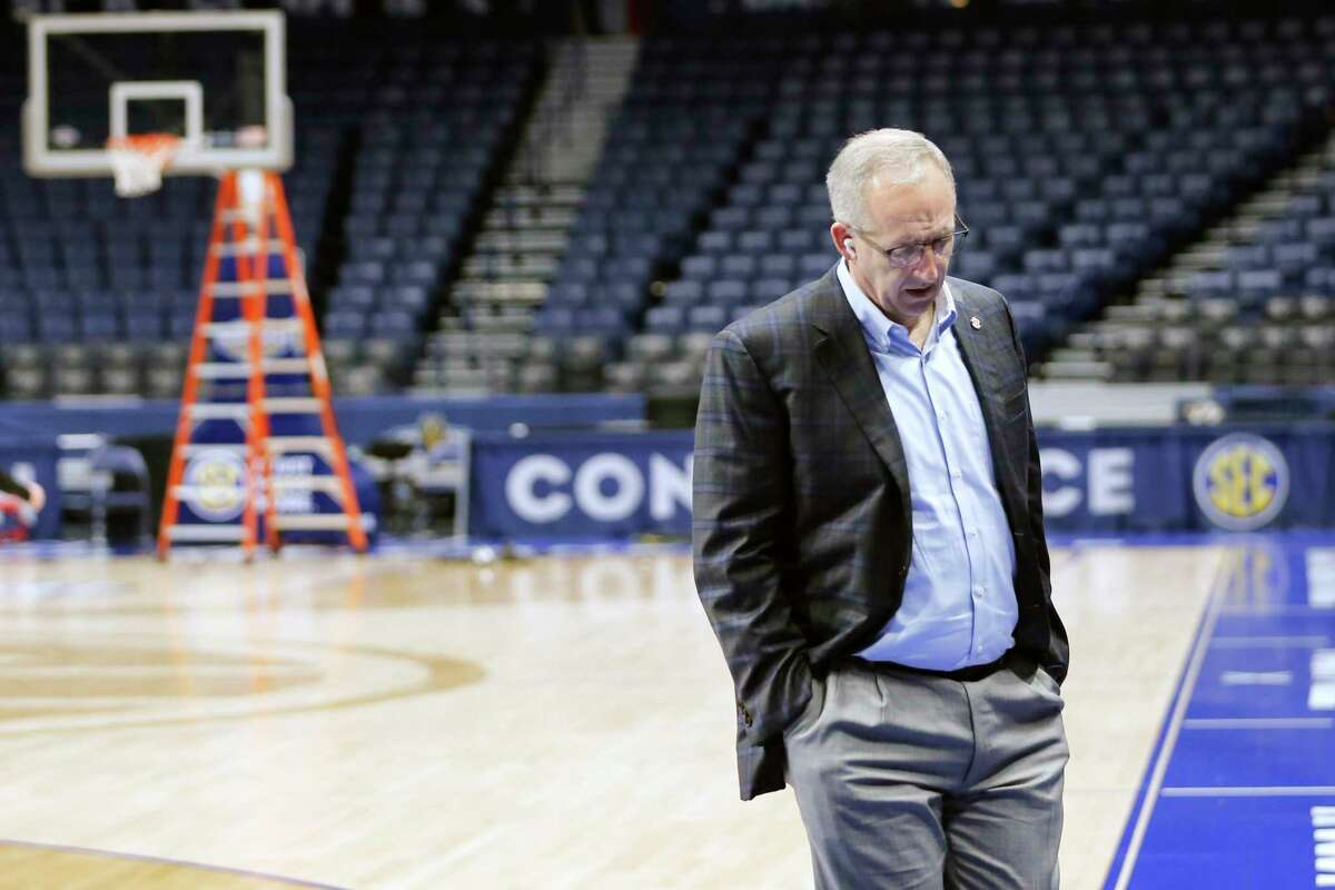 Greg Sankey, commissioner of the Southeastern Conference, walks across the basketball court as the venue is dismantled after the remaining NCAA college basketball games in the Southeastern Conference tournament were canceled, Thursday, March 12, 2020, in Nashville, Tenn. The tournament was canceled Thursday due to coronavirus concerns. (AP Photo/Mark Humphrey)