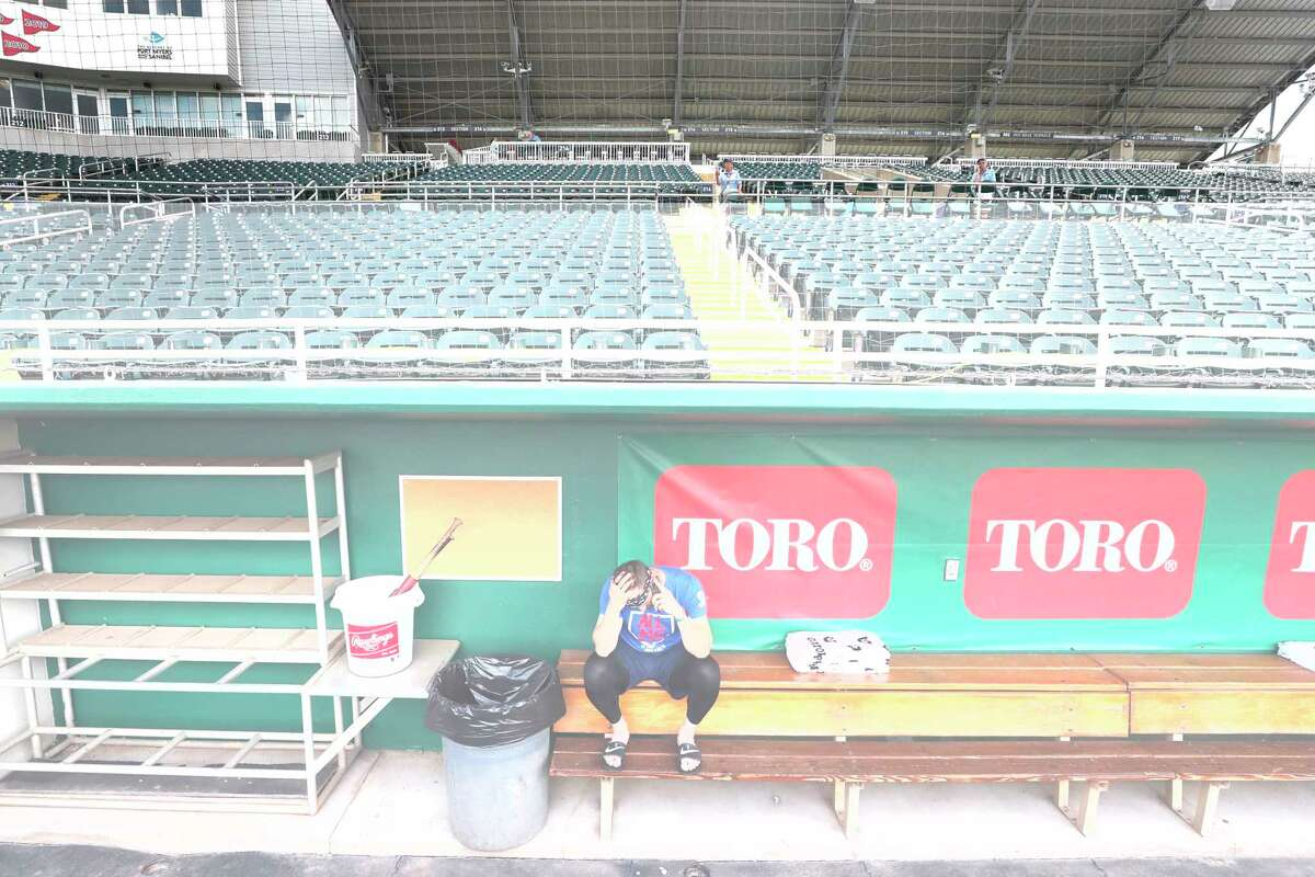 Minnesota Twins catcher Mitch Garver talks on his phone in an empty Hammond Stadium, Thursday, March 12, 2020, in Fort Myers, Fla. Major League Baseball has suspended the rest of its spring training game schedule because if the coronavirus outbreak. MLB is also delaying the start of its regular season by at least two weeks. (AP Photo/Elise Amendola)