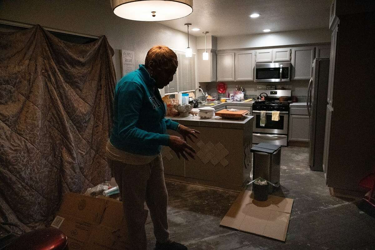 Sylvia Lewis works during the events at Chase and other venues and will lose all her income. She stands in her home, under renovation, where she will be installing a new floor on Thursday, March 12, 2020, in Antioch, Calif.
