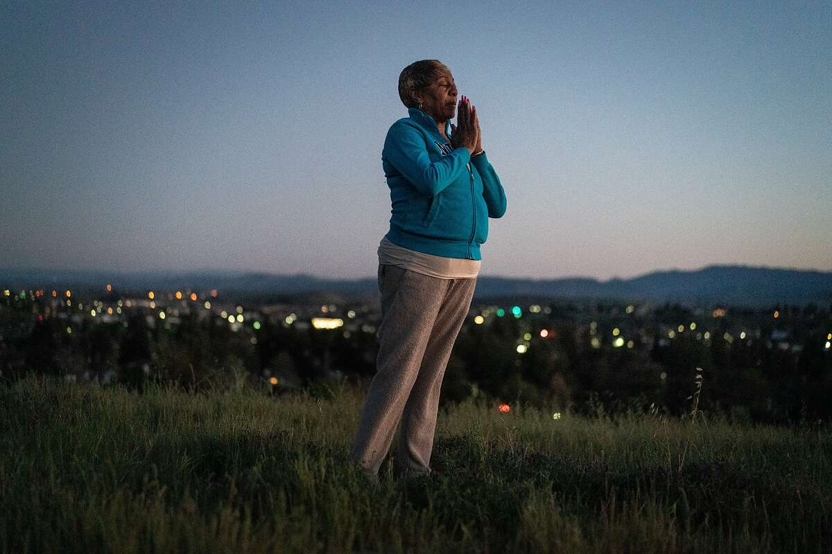 Sylvia Lewis works during the events at Chase and other venues and will lose all her income. She stand on a hill behind her home, praying for help on Thursday, March 12, 2020, in Antioch, Calif.