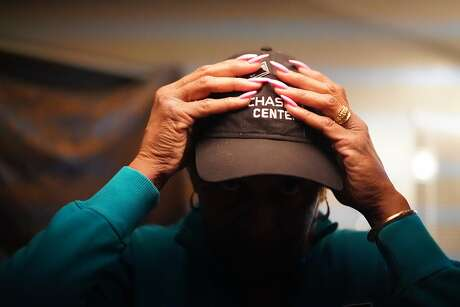 Sylvia Lewis works during the events at Chase and other venues and will lose all her income.  She puts on her cap in her home as she wonders how she�ll pay for its mortgage on Thursday, March 12, 2020, in Antioch, Calif.
