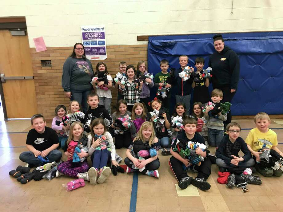 Andrea DeJong's class at Jefferson Elementary School are pictured with the socks and mittens that were donated to the students at the school by the Women of Steel Local 12585 United Steelworkers and an anonymous donor. (Courtesy photo)