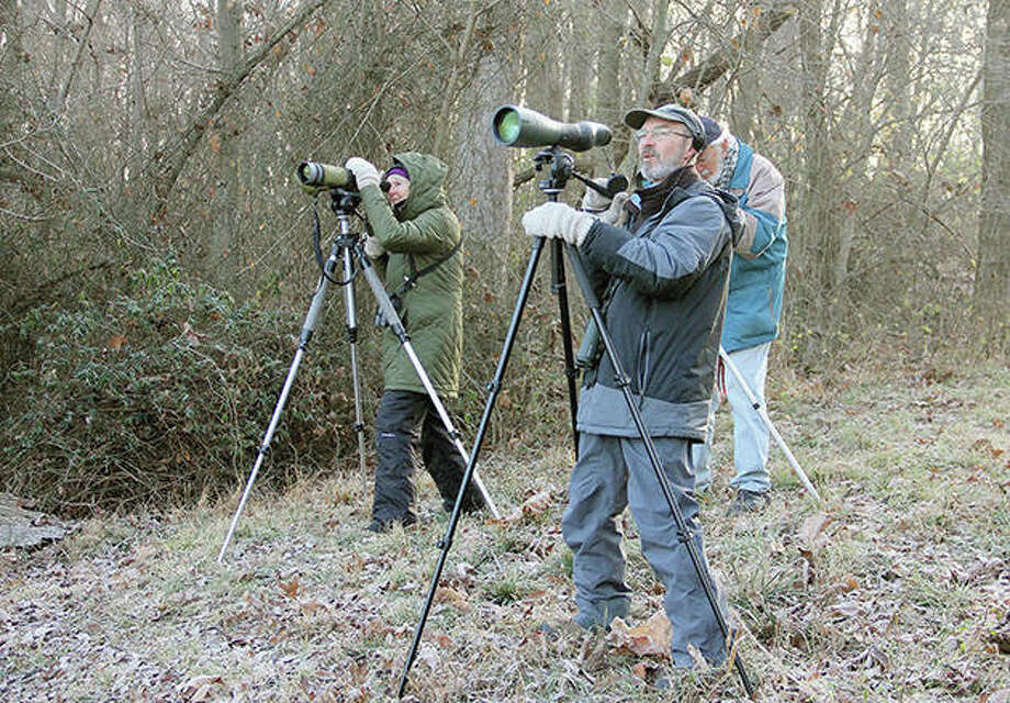 Judy Groskind (left), Don Mullison (right) and John Van Dyk scan an area of Crab Orchard National Wildlife Refuge in Illinois for water birds. The volunteers were conducting a weekly count at the refuge. Photo: Les Winkeler | Southern Illinoisan (AP)