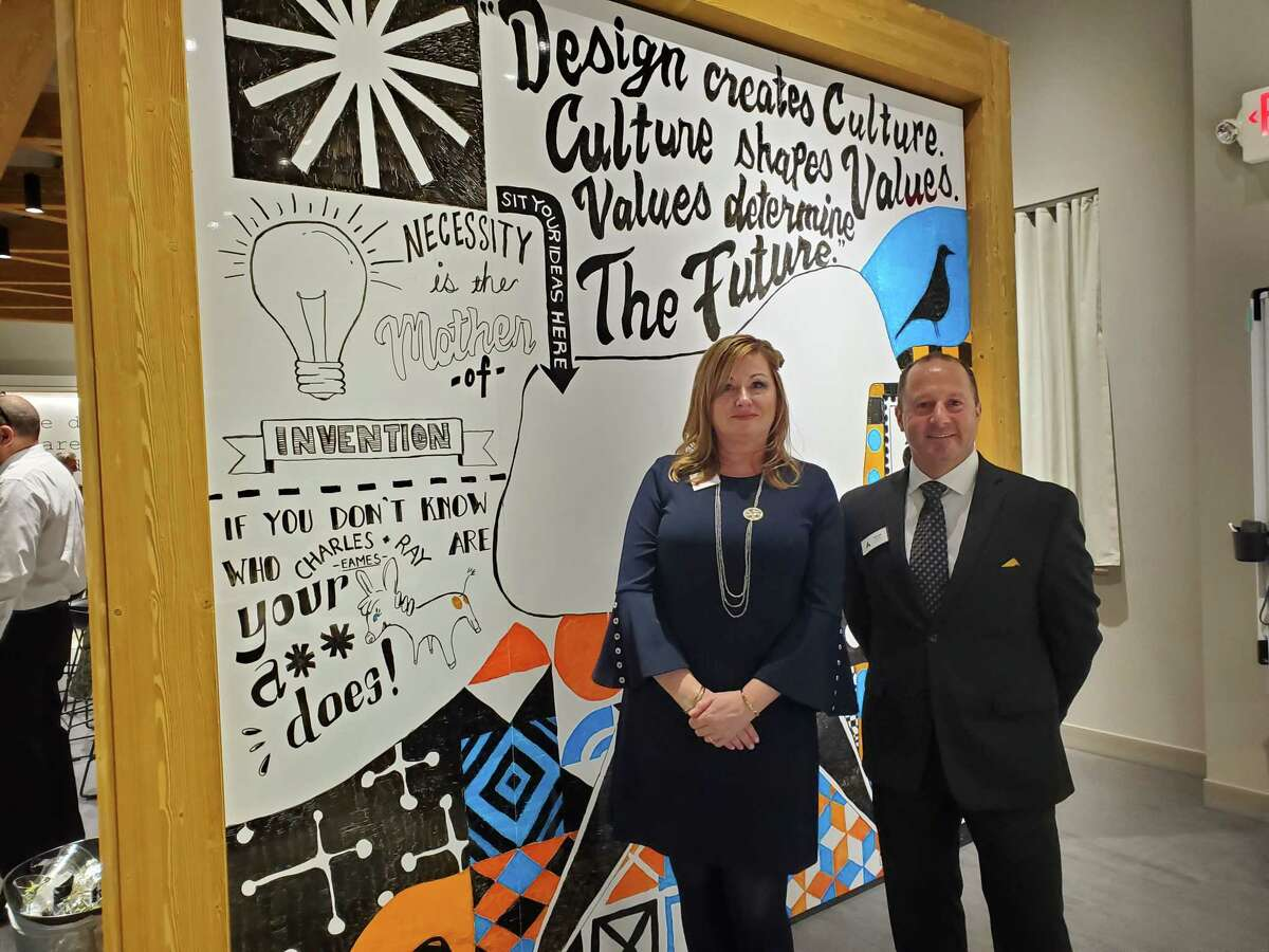 Pati Barclay, left, territory manager for Accent Furniture, and Michael Gleasman, CEO, pose in front of artwork by artist Jason Reyes. (Photo: Leigh Hornbeck/Times Union)
