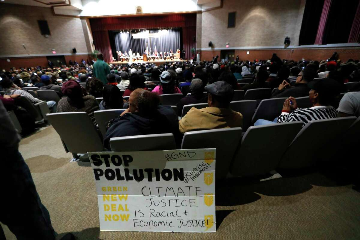 """A """"stop Pollution"""" sign is shown at a town hall about a cancer cluster identified in Houston. The town hall was hosted by Congresswoman Sheila Jackson Lee at Wheatley High School, in Houston, Tuesday, Jan. 21, 2020."""