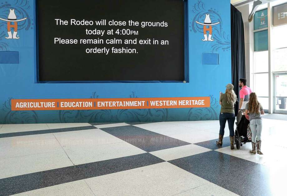People look at a sign telling visitors to leave the Houston Livestock Show and Rodeo after its cancelation was announced due to concerns about COVID-19 on Wednesday, March 11, 2020, at NRG Center in Houston. Photo: Jon Shapley, Houston Chronicle / Staff Photographer / © 2020 Houston Chronicle