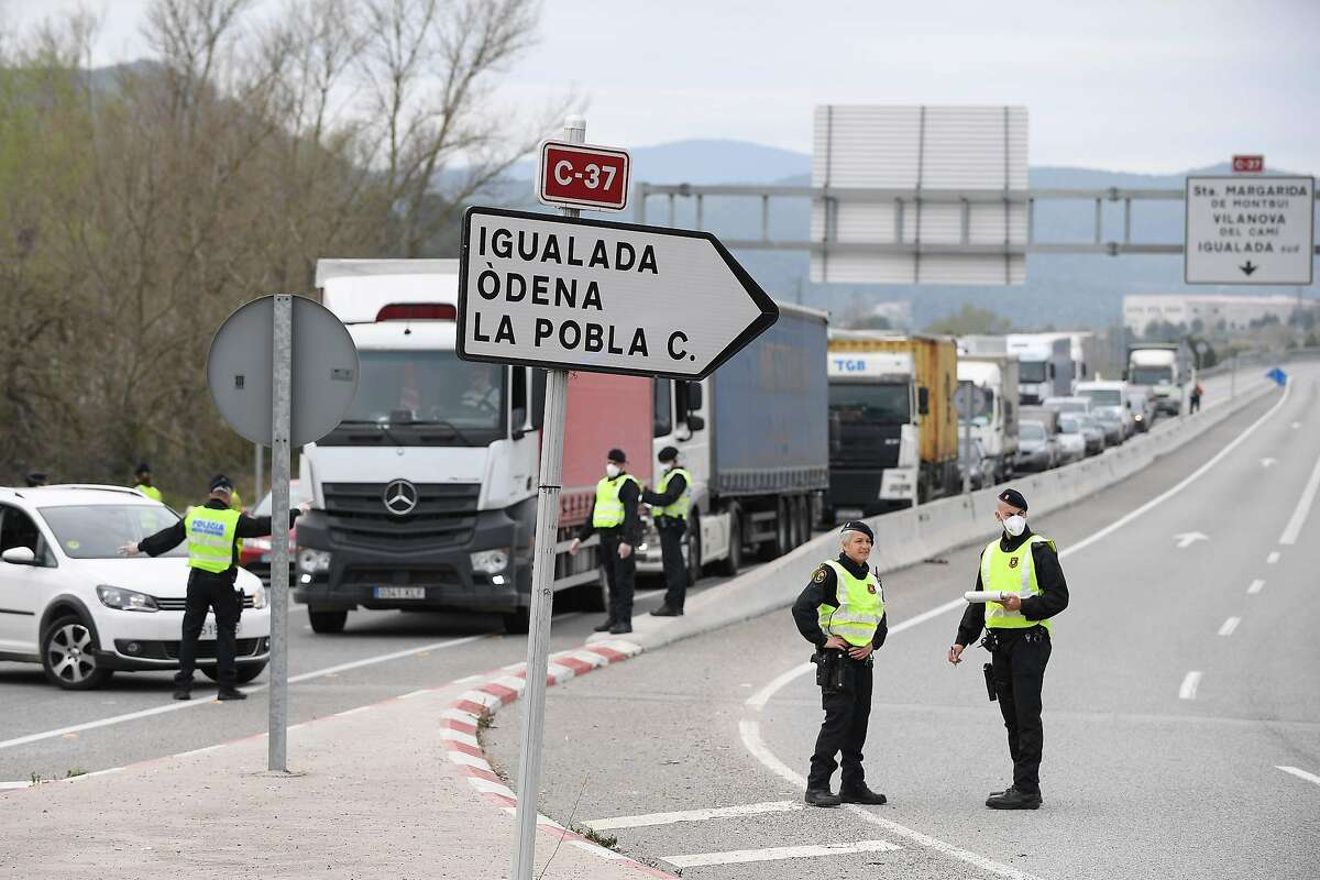 """Members of the Catalan regional police force Mossos d'Esquadra stop the traffic on the N-II road outside the town of Igualada on March 13, 2020, after four towns in Spain's northeastern Catalonia region were put under quarantine. - The 66,000 inhabitants of the localities of Igualada, Odena, Santa Margarida de Montbui and Vilanova del Cami """"cannot leave their urban core"""" although they can leave their homes, a statement said, citing instructions from Catalonia's governor. (Photo by Josep LAGO / AFP) (Photo by JOSEP LAGO/AFP via Getty Images)"""