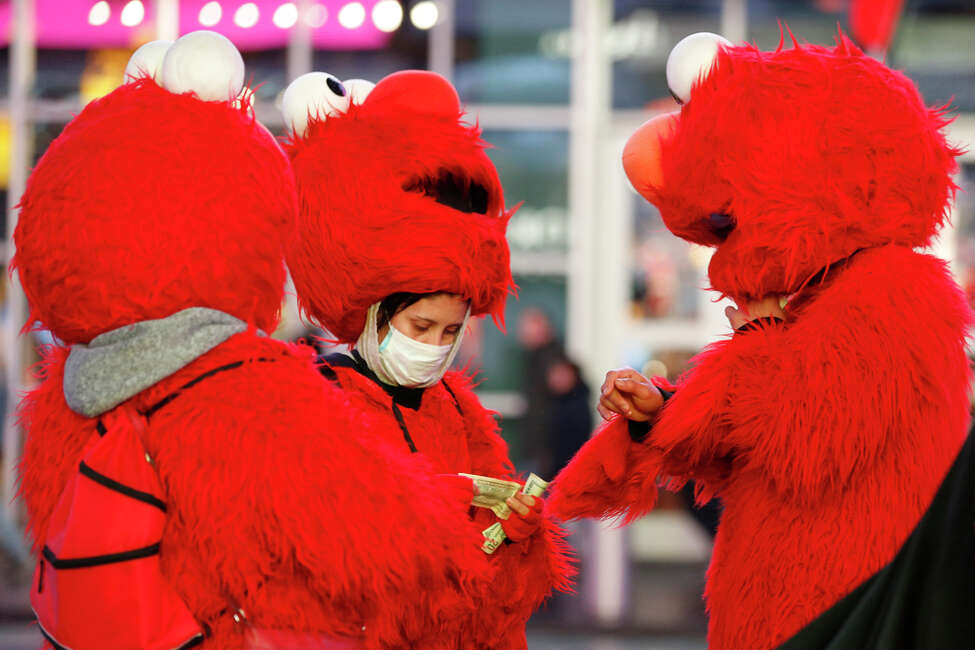 A mask-wearing costumed character in Times Square looks through bills during a lull in activity Thursday, March 12, 2020, in New York. Earlier Thursday, Gov. Andrew Cuomo banned gatherings of 500 or more people.